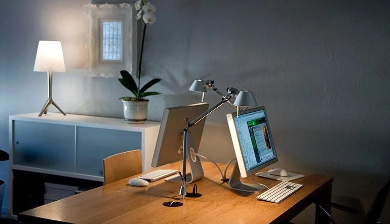 A casual home office setting with Monitors, desks and Lamps